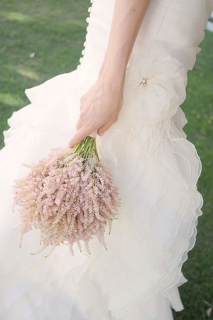 A blush pink astilbe bouquet compliments the softeness of this gown's romantic ruffled skirt