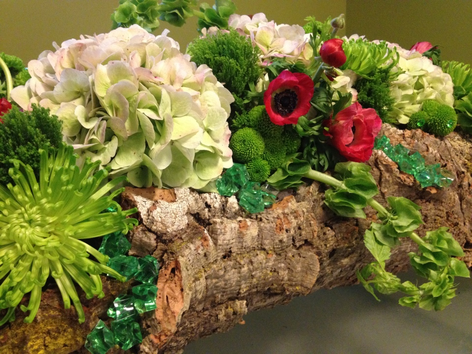 Centerpieces of hydrangea, Spider Mums, Button Poms, Belles of Ireland, Green Trick Dianthis in cork wood bases. Accents of Red Anemones & Emerald Crystals
