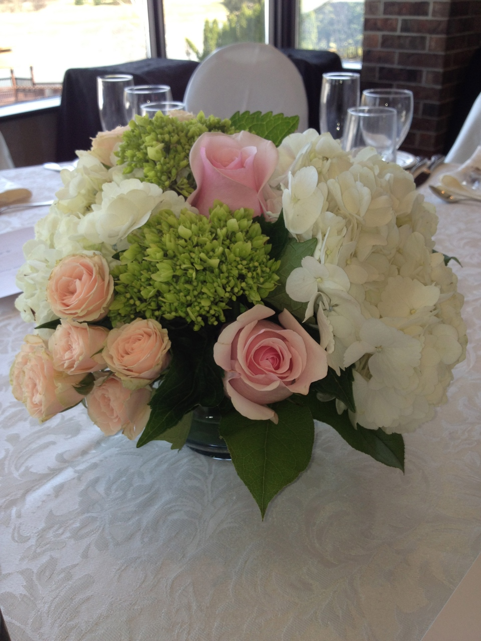 Low Centerpieces of white and green hydrangea with pink and peach roses,