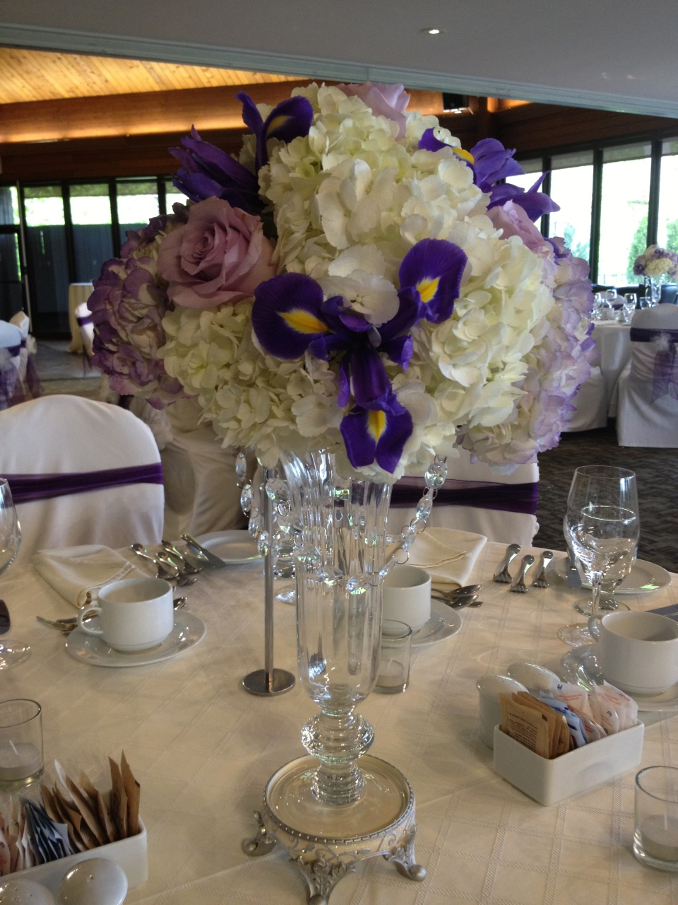 Centerpieces of hydrangea, roses and purple iris