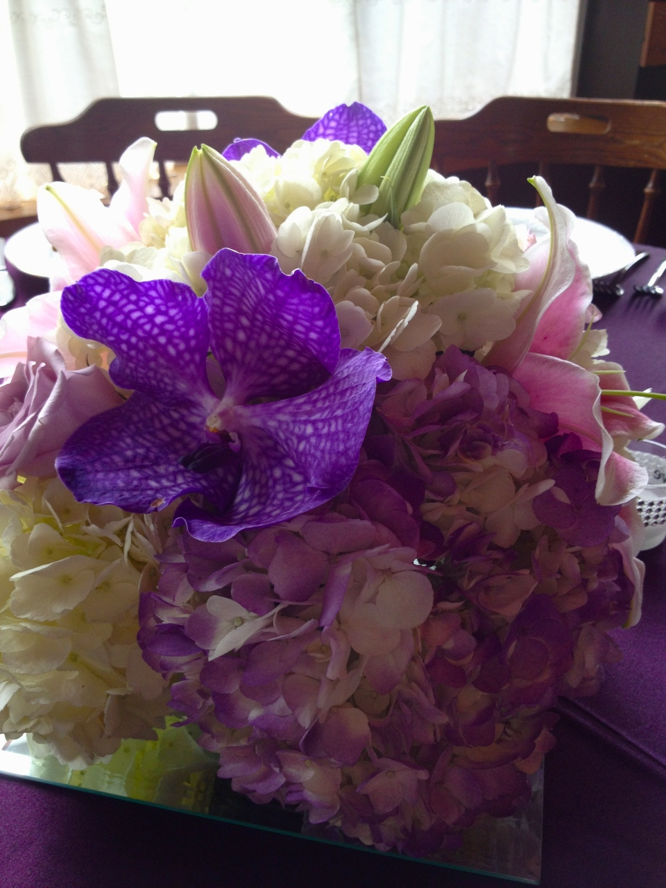 Purple and pink centerpiece of vanda orchids, lilies and hydrangea