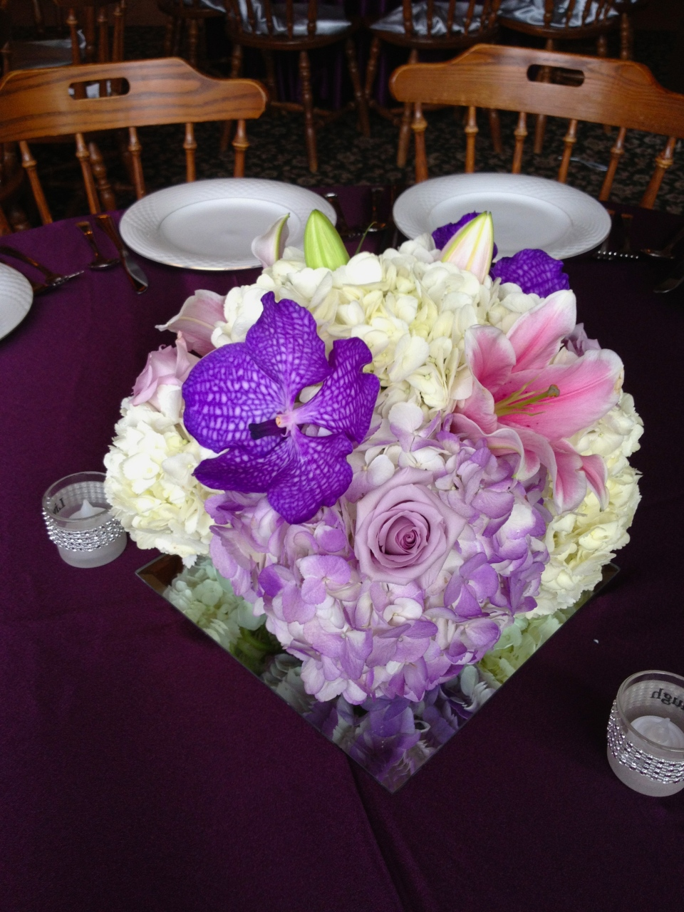 Hydrangea, lilies, roses and vanda orchids in shades of purple and pink.