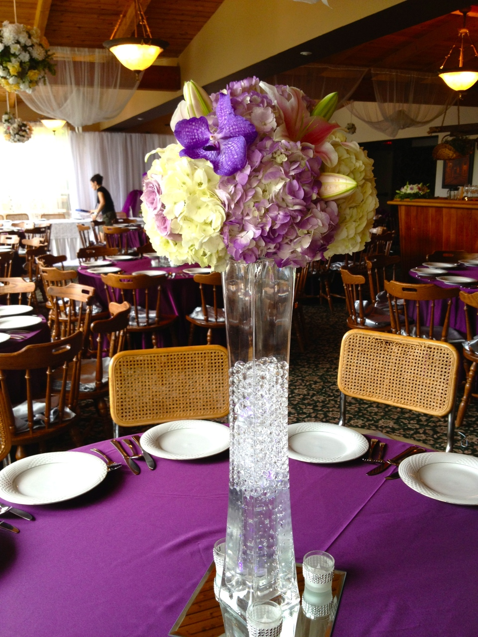 Tall purple and pink centerpiece with hydrangea, lilies and vanda orchids