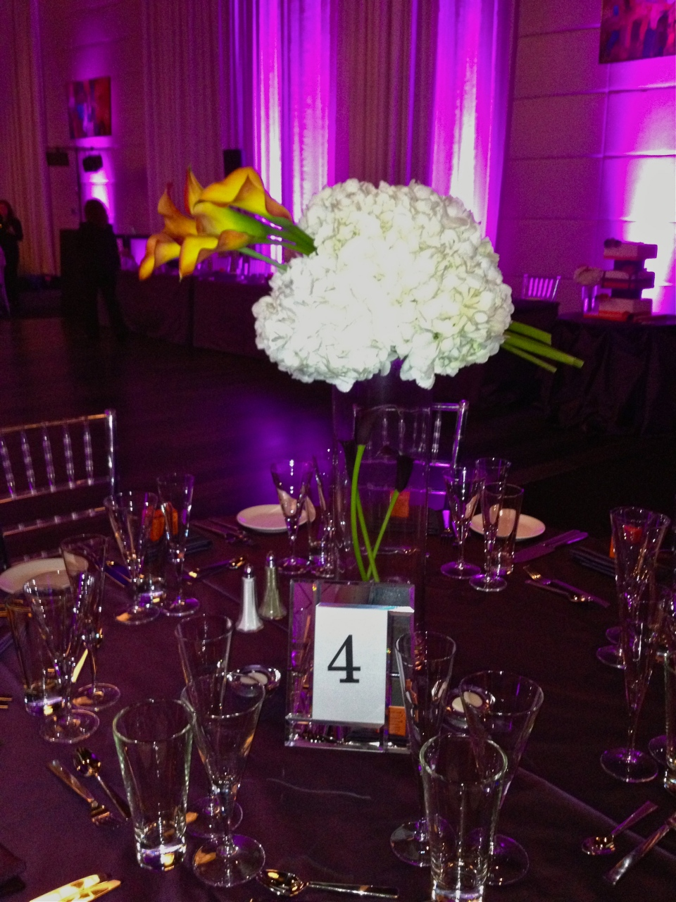 Calla lilies appear to be stuck completely through the hydrangea globe of the tall centerpieces.