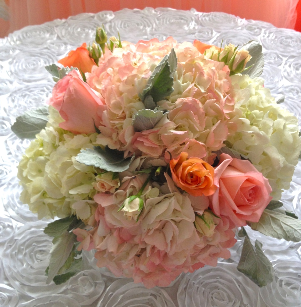 Pink, peach and ivory centerpieces with hydrangea, roses and dusty miller