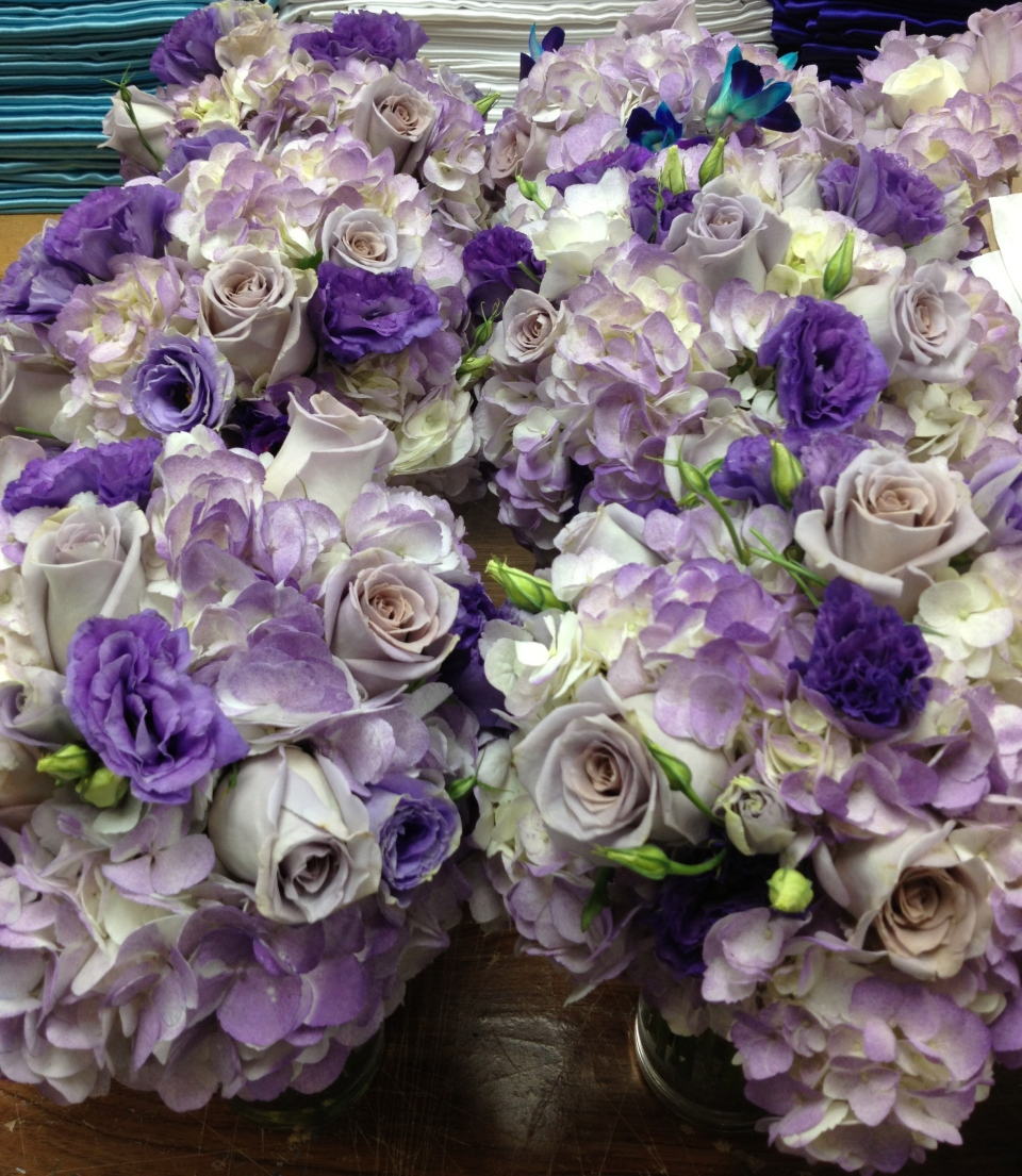 Bridesmaids bouquets of purple hydrangea, roses and lisianthis.