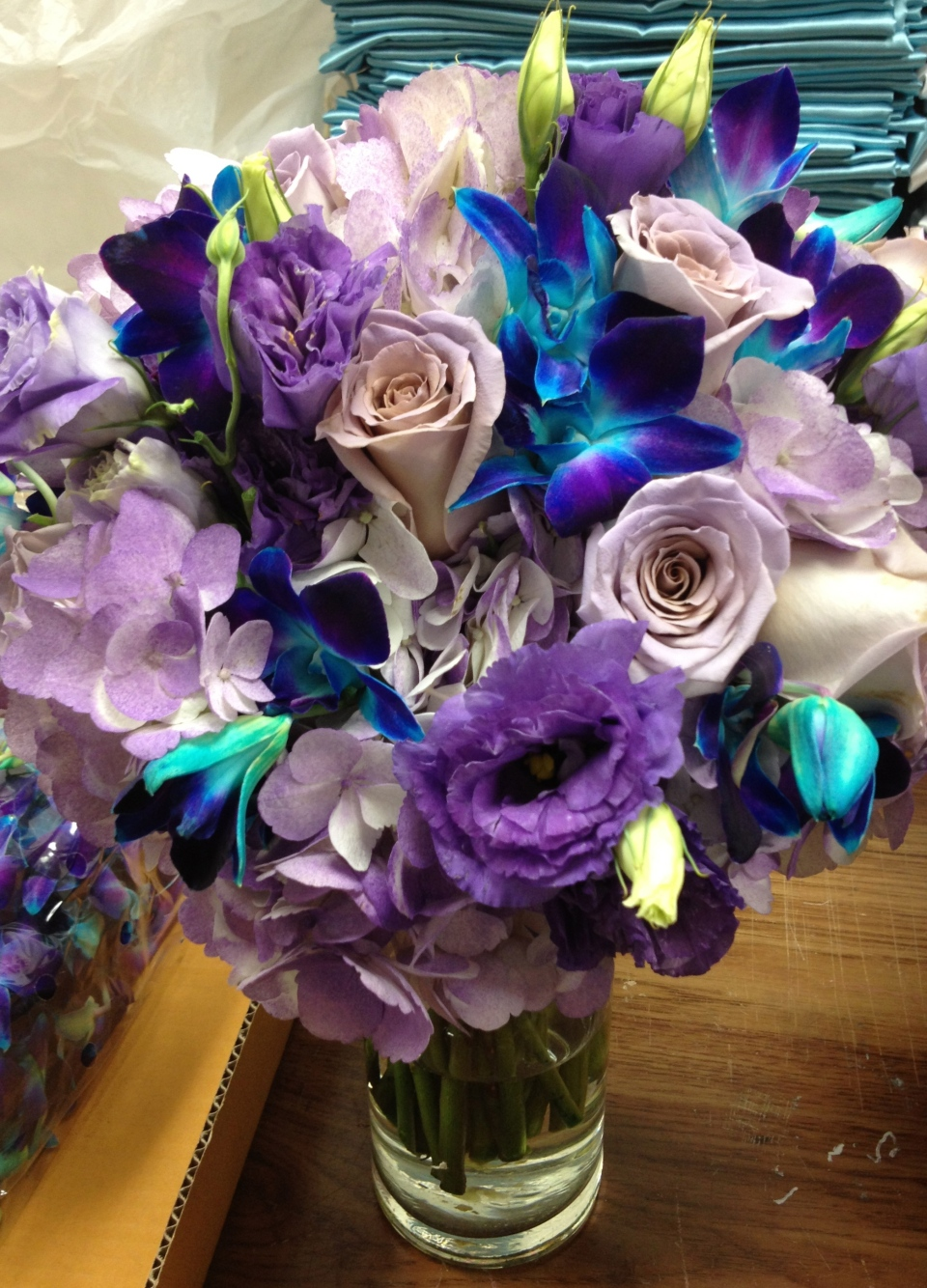 Purple and turquoise bridal bouquet with orchids, lisianthus, roses and hydrangea.