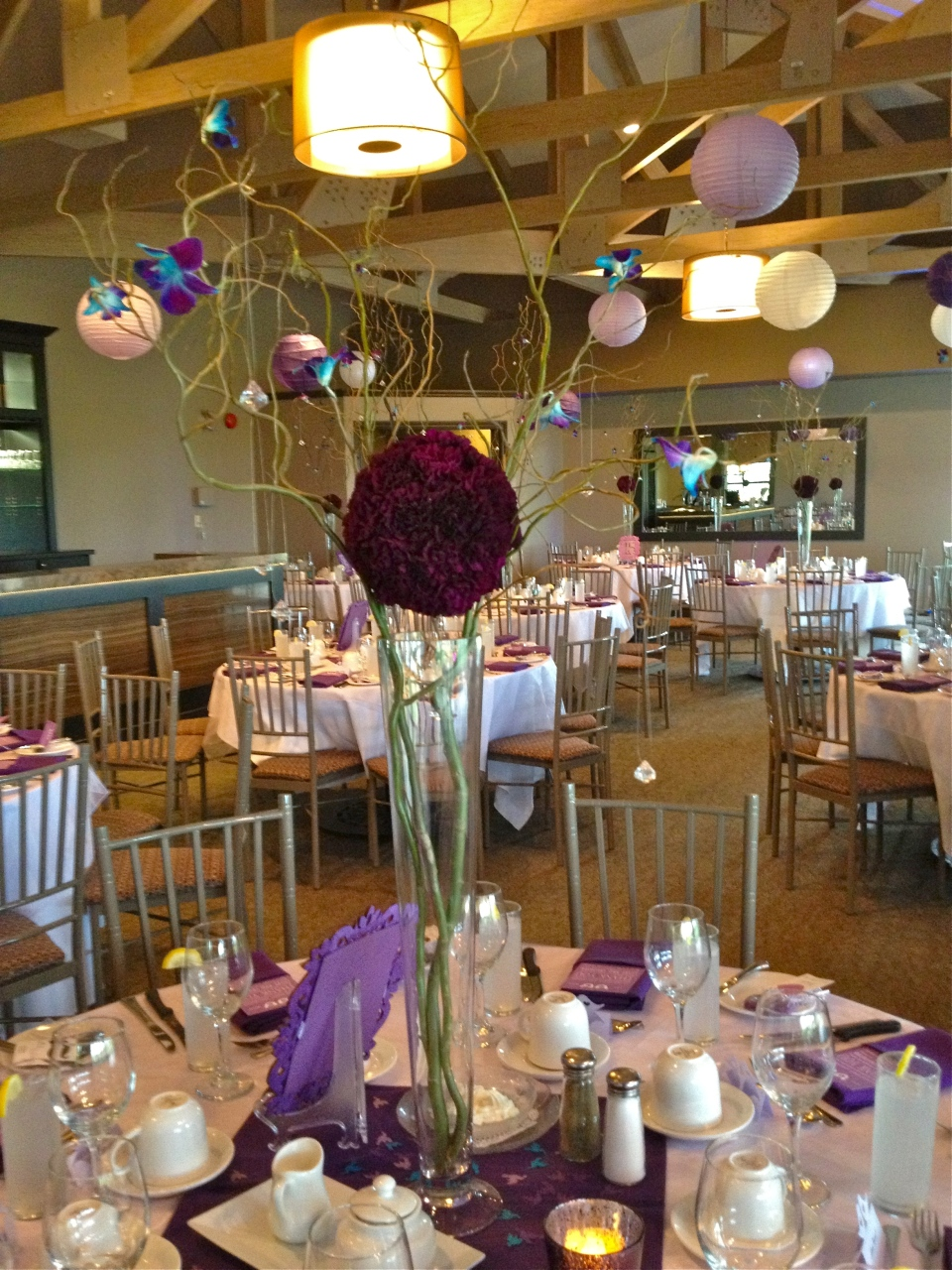 Carnation globe and wired orchids on curly willow branches centerpiece