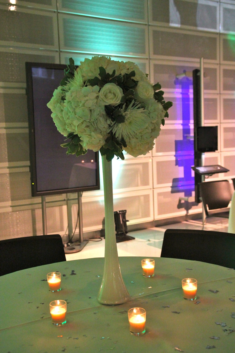 Tall centerpiece of spider mums, roses and hydrangea perched on a white glass vases