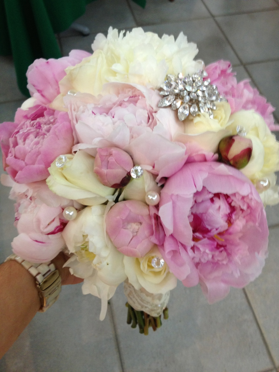 A vintage brooch and crystal and pearl pins add flair to this simple peony bouquet.