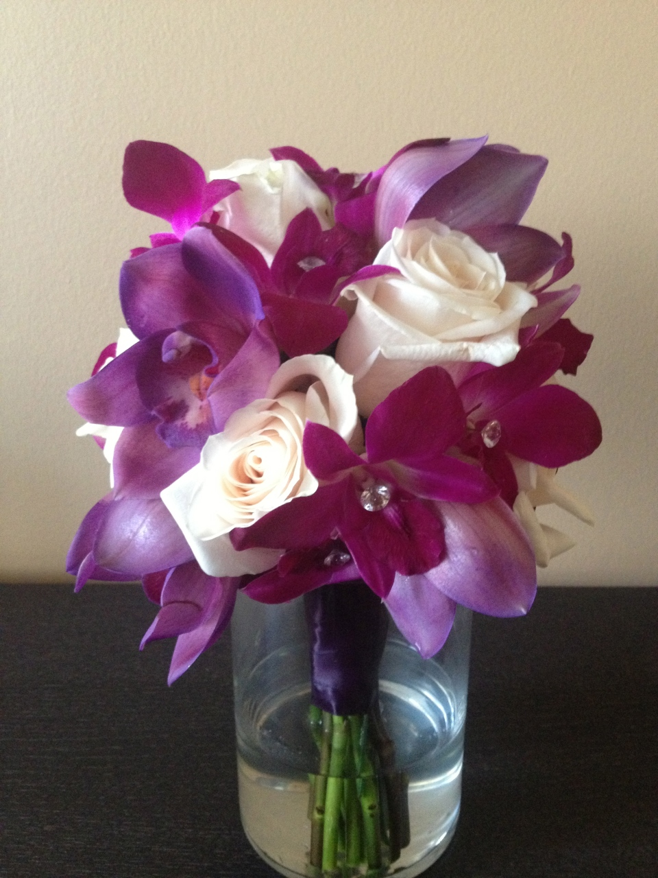 Purple cymbidium and dedrobium orchid bouquet with white roses