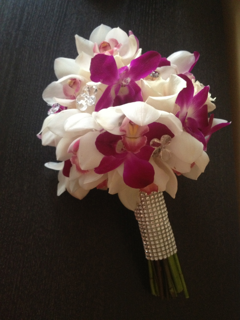 Bridal bouquet of cymbidium and dendrobium orchids with roses and crystal detailing