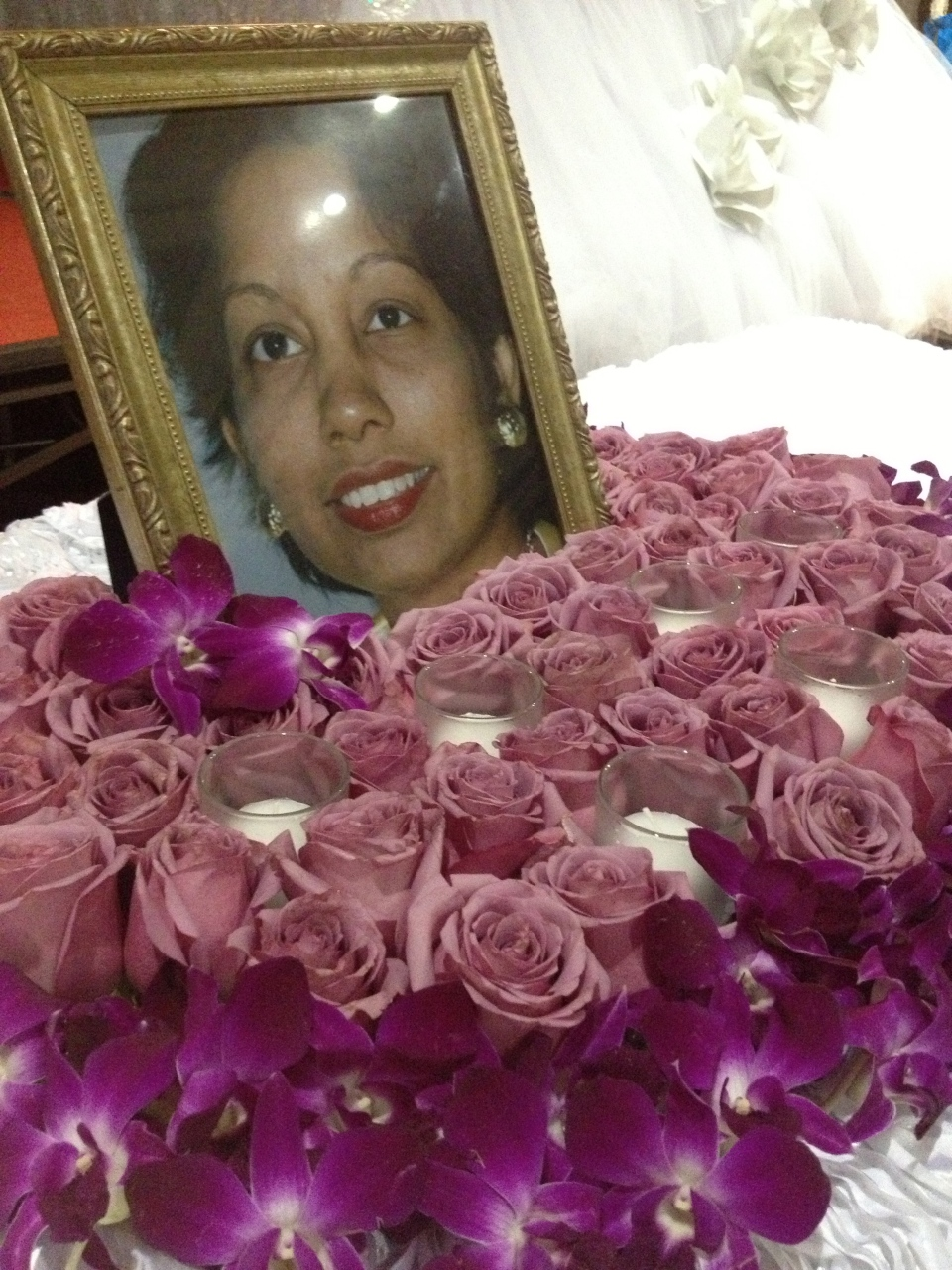 A bed of purple roses and dendrobium orchids for the memorial table.