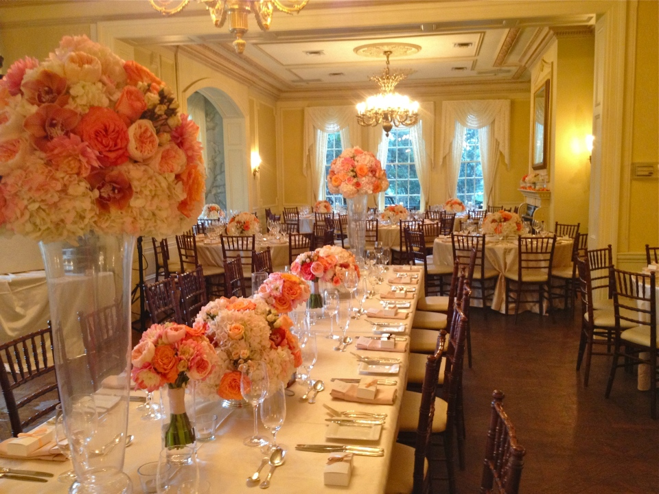 The gallery head table covered in coral and peach floral arrangements