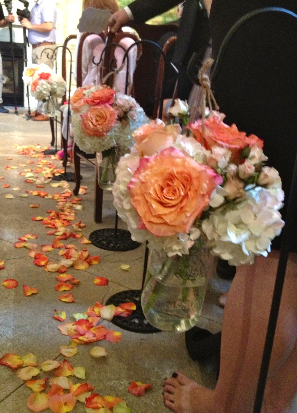 Aisle markers of coral cabbage roses, peach spray roses and hydrangea