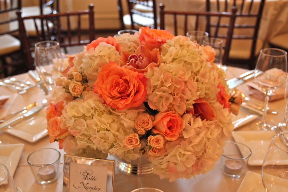 Coral and peach centerpieces of hydrangea, roses, spray roses & cymbidium orchids