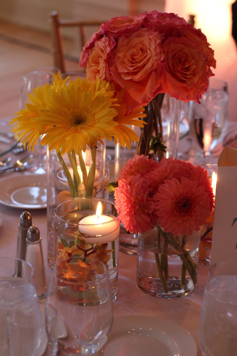 Grouping of roses, gerberas and dahlias with submerged orchid floating candles.