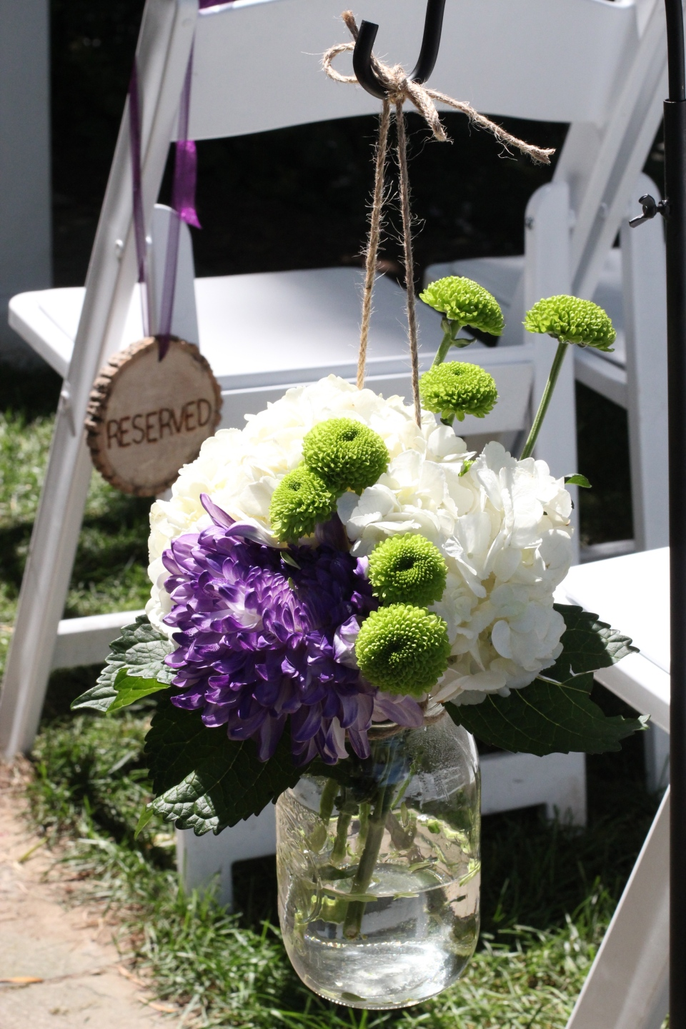 Shepherds hooks lined the aisle with mason jars filled with hydrangea, mums and button poms.