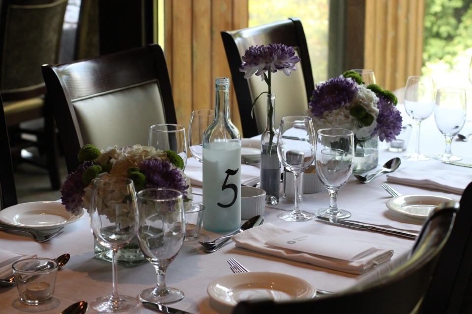 Small arrangements of hydrangea, button poms and mums line the guest tables
