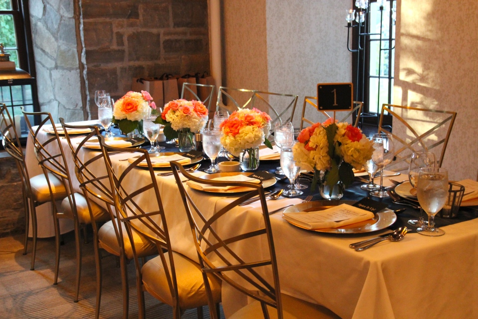 Gallery tables with navy runners, gold chargers and our peach & coral florals