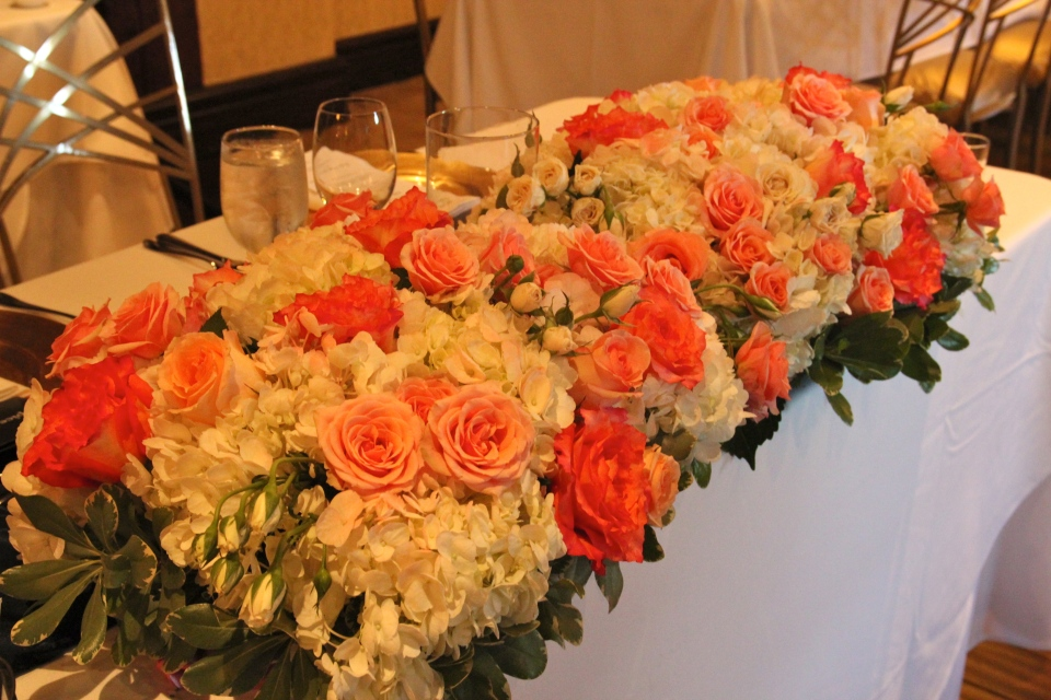 Head table arrangement loaded with coral and peach roses