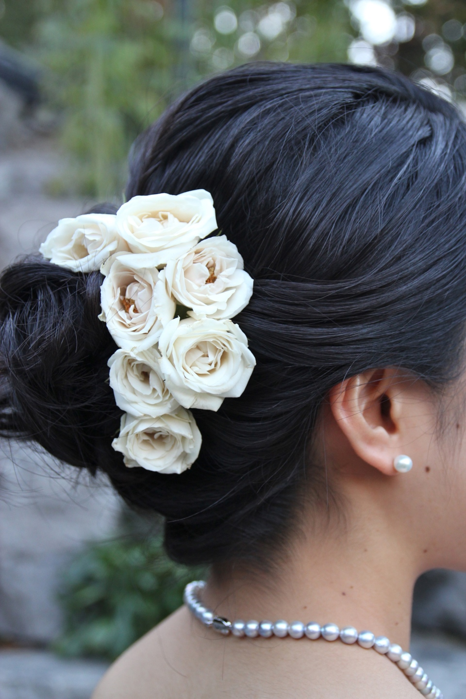 The bride's hairstyle with fresh ivory spray roses.