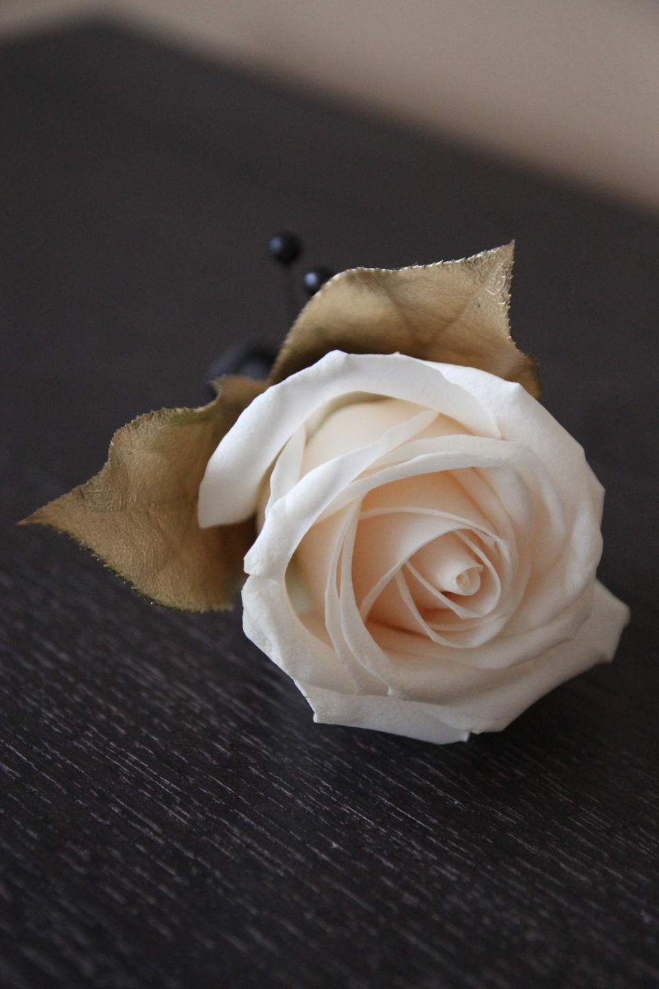 Groom's rose boutonniere accented with gold leaves