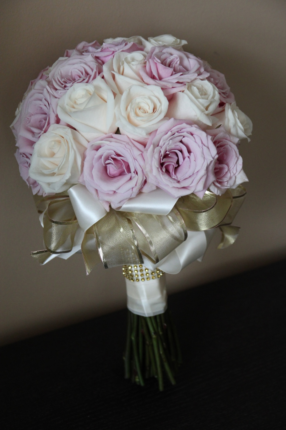 Bridal bouquet of blush and ivory roses with gold ribbon detailing.
