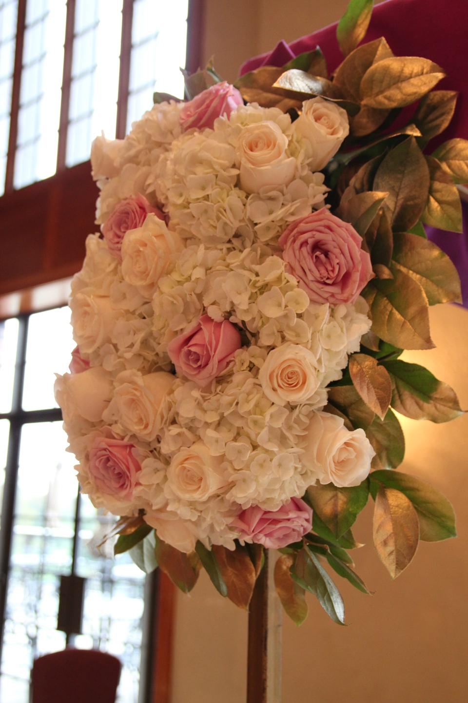 Chuppah arrangement of hydrangea, roses and gold leaves
