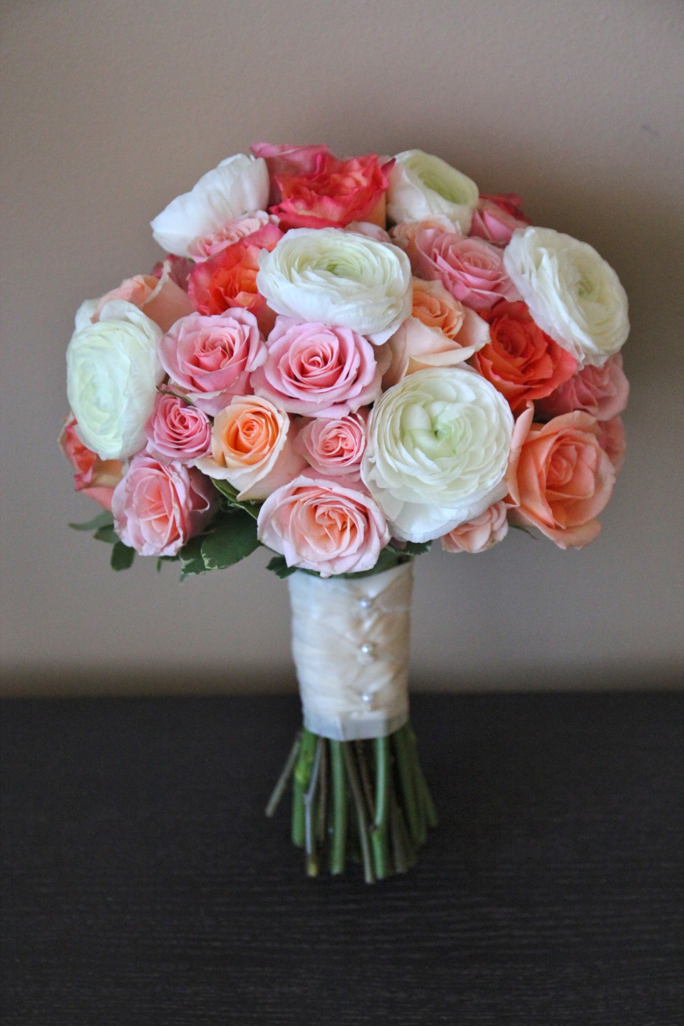 Bridal bouquet of roses, cabbage roses, spray roses & ranunculus in shades of peach, coral & white