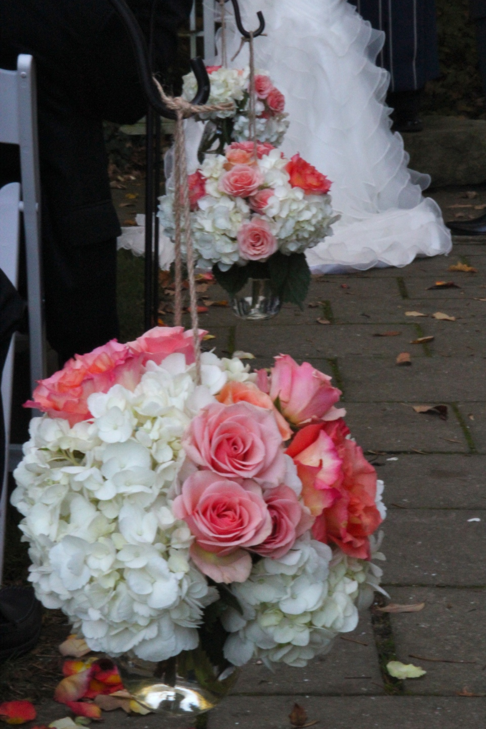 Aisle markers of white hydrangea with coral and pink roses.