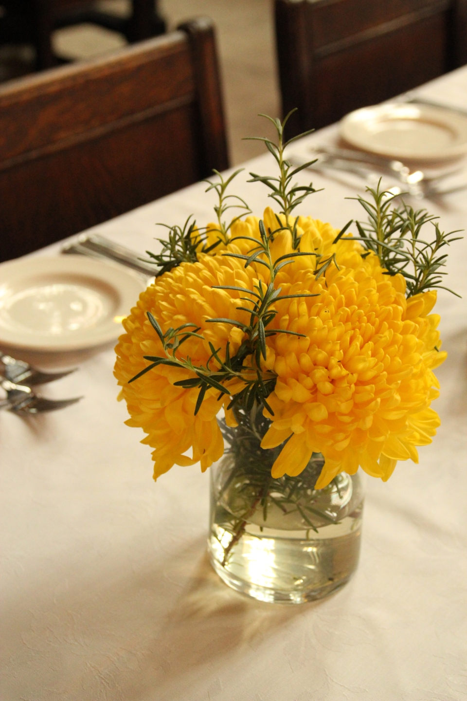 Textured yellow mums and rosemary sprigs