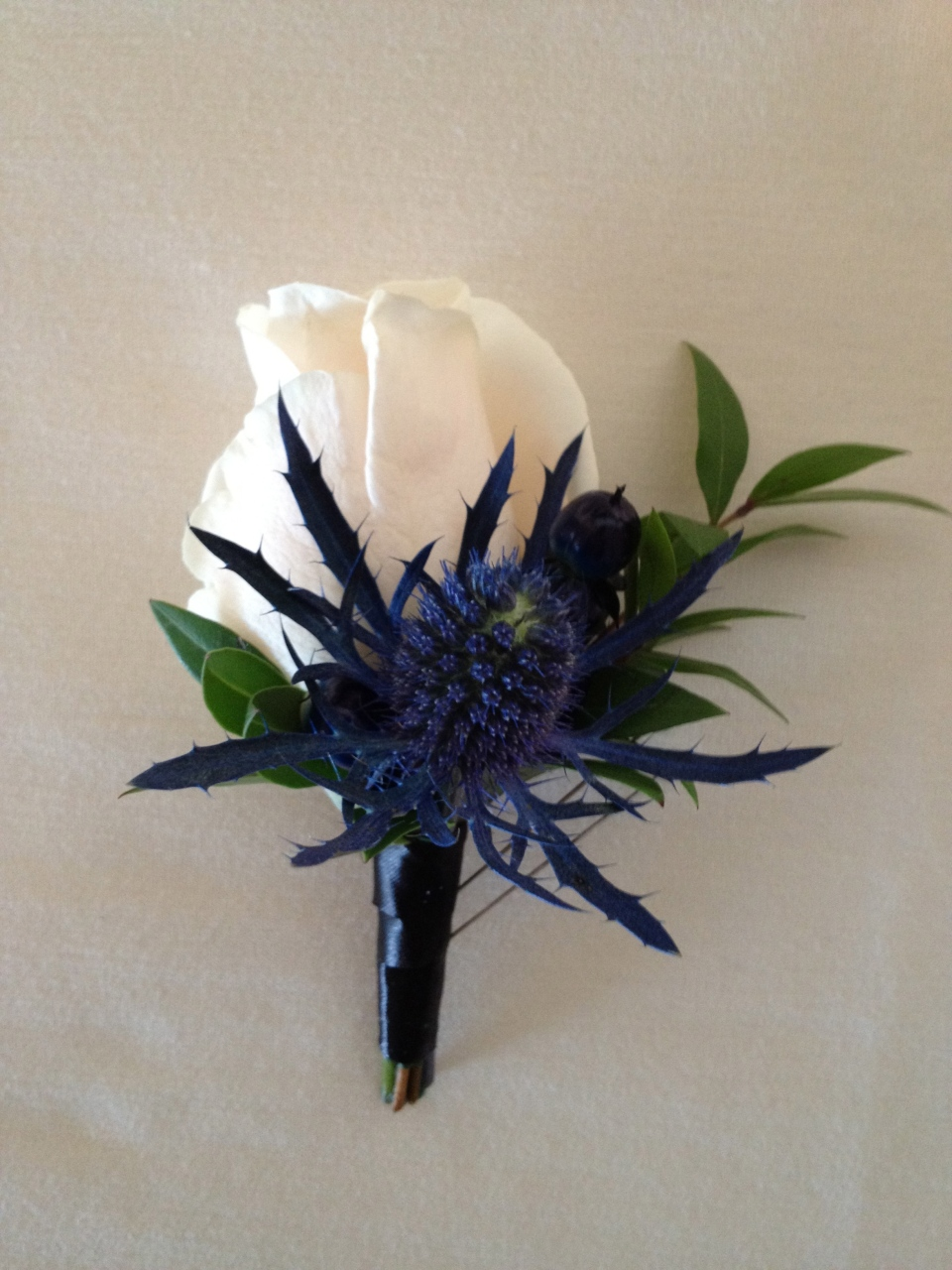 Cream rose boutonniere with blue thistle accent