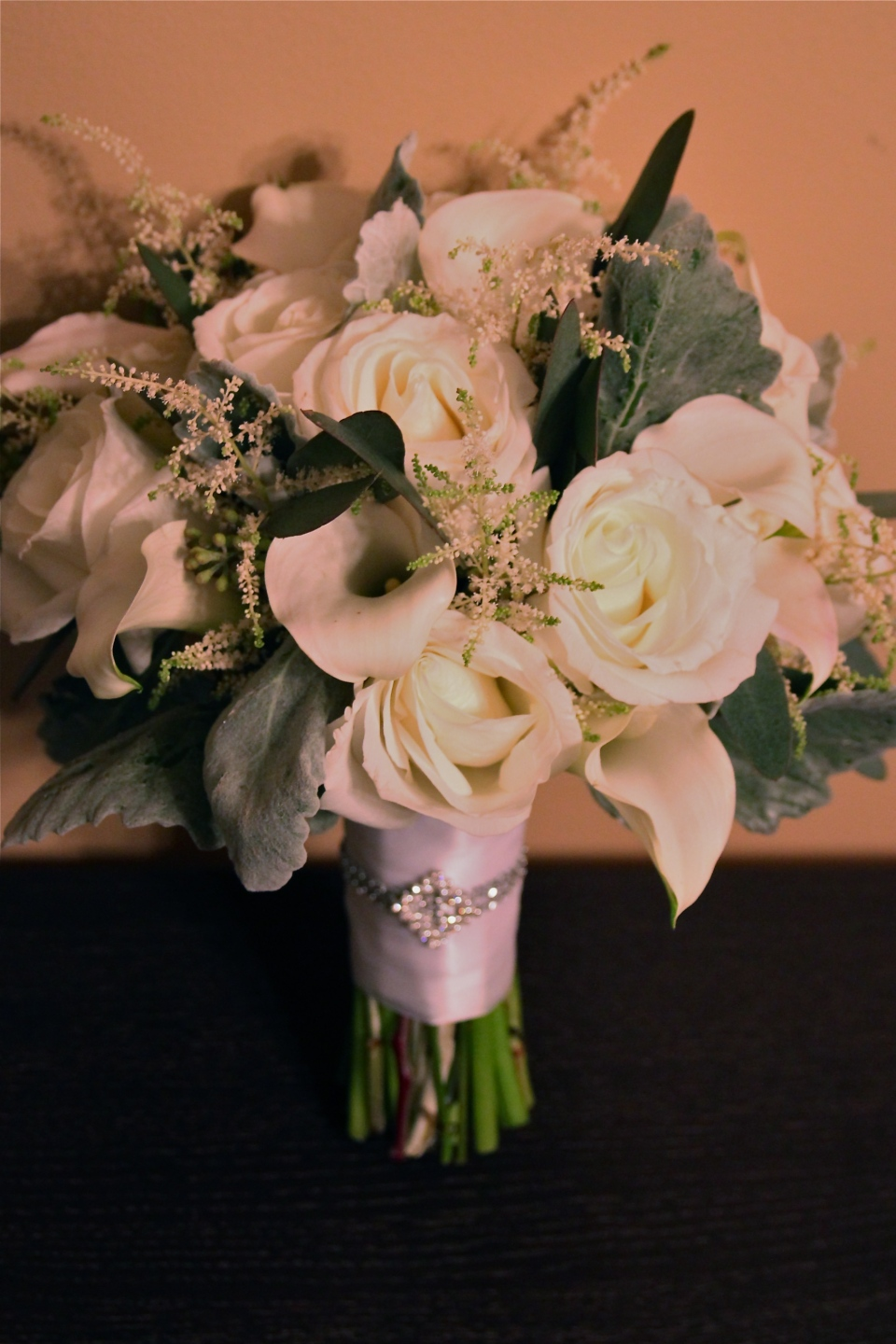 Winter white bridal bouquet of roses, calla lilies, astilbe, dusty miller and seeded eucalyptus.