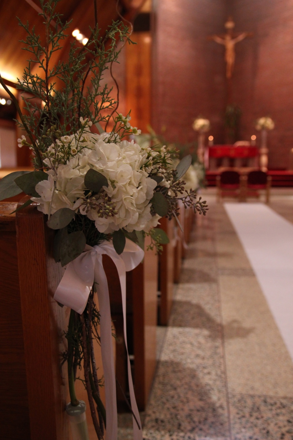 Pew markers of hydrangea, wax flower, evergreens & curly willow tied with white satin ribbon.
