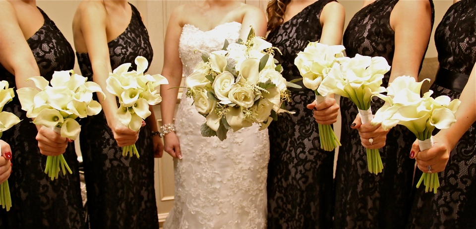 Sleek white calla lily bouquets for the bridesmaids in black lace gowns