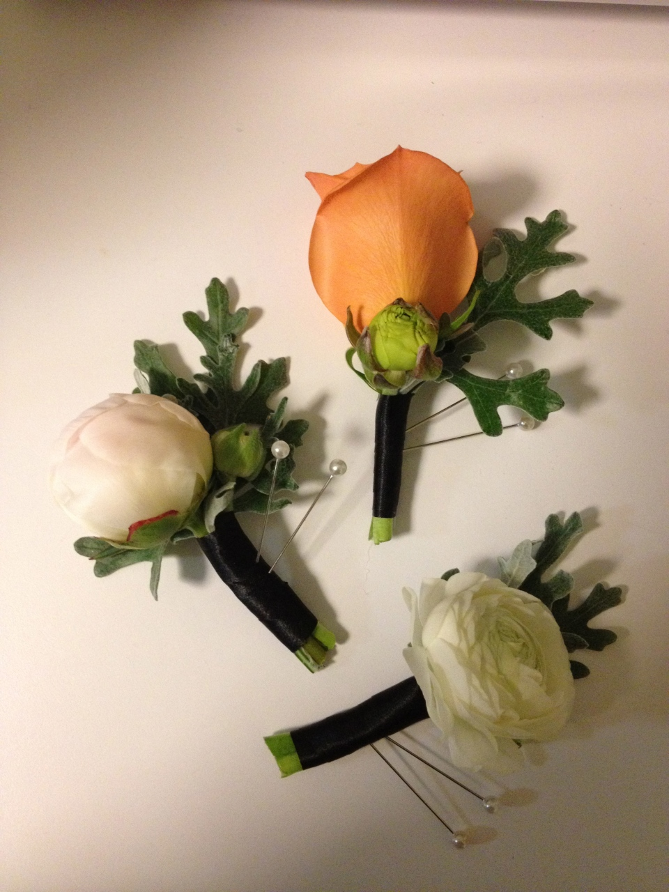 Selection of boutonnieres: Peony bud, rose and ranunculus all accented with dusty miller