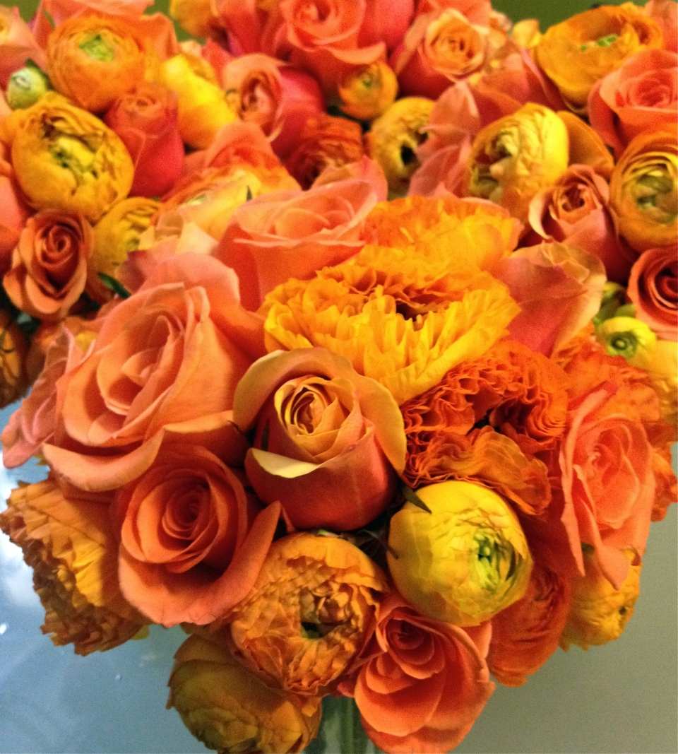 Vibrant orange roses and ranunculus for the bridesmaids bouquets