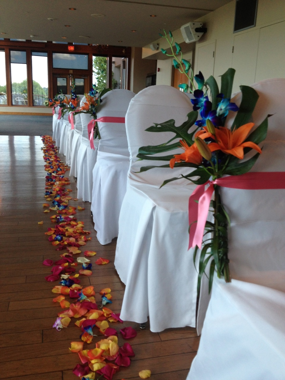 Orange lilies, blue orchids & tropical leaves for aisle markers