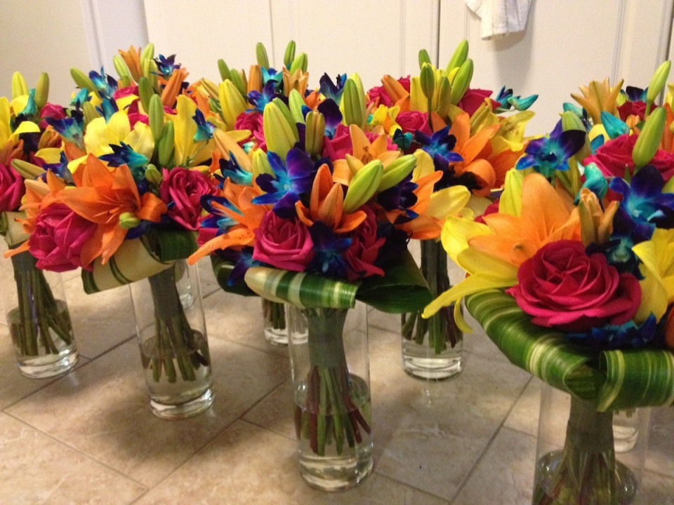 Tropical bridesmaids bouquets combined lilies, roses & dendrobium orchids with folded leaf collar.