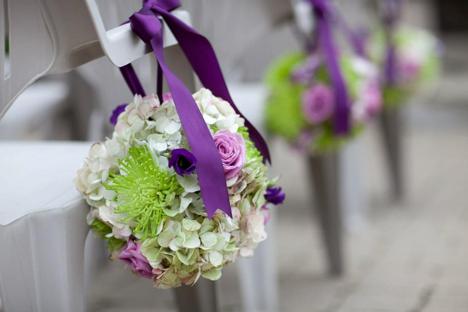 Sweet purple and green floral pomanders line the aisle
