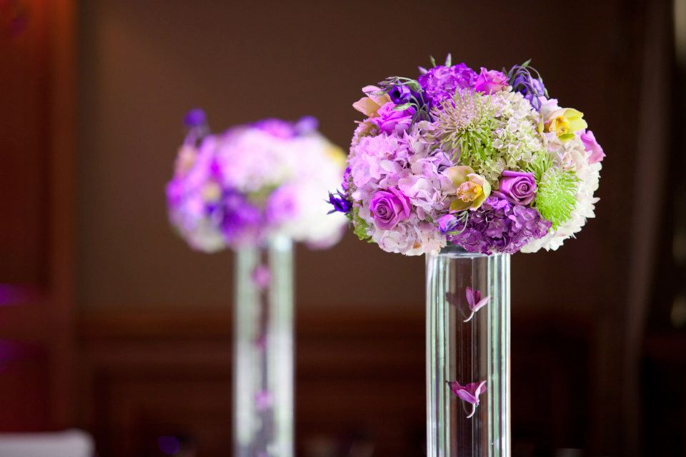 Strung orchids float down the center of the vases of tall purple and green centerpieces