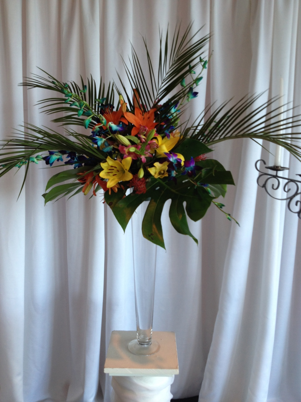 Altar pieces combined tropical leaves with bright lilies, protea, orchids & roses