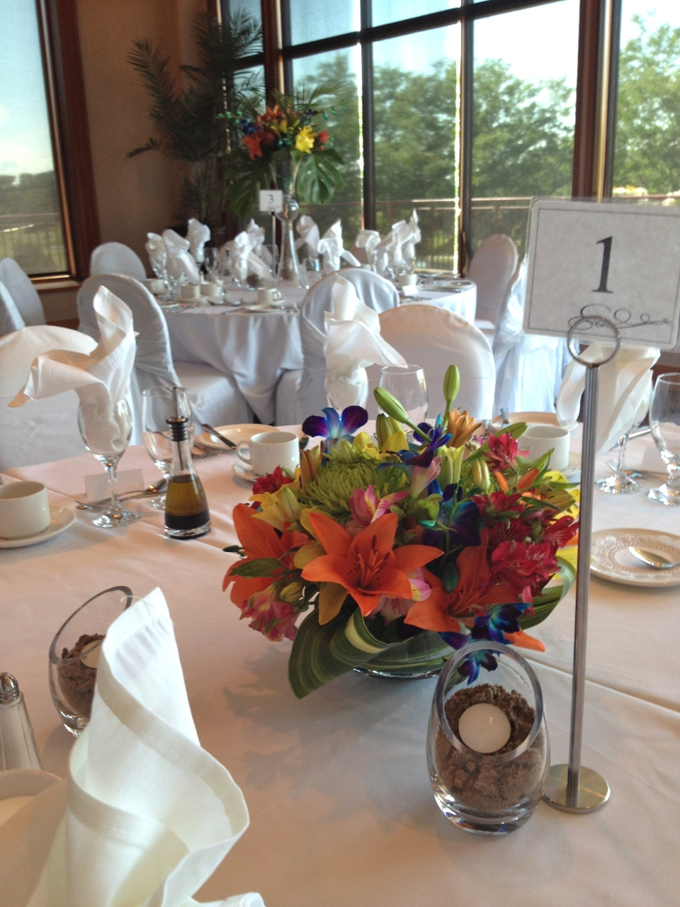 Low tropical centerpieces with sand filled candle holders