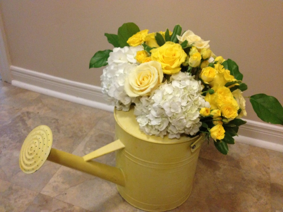 Yellow vintage watering can with floral detailing