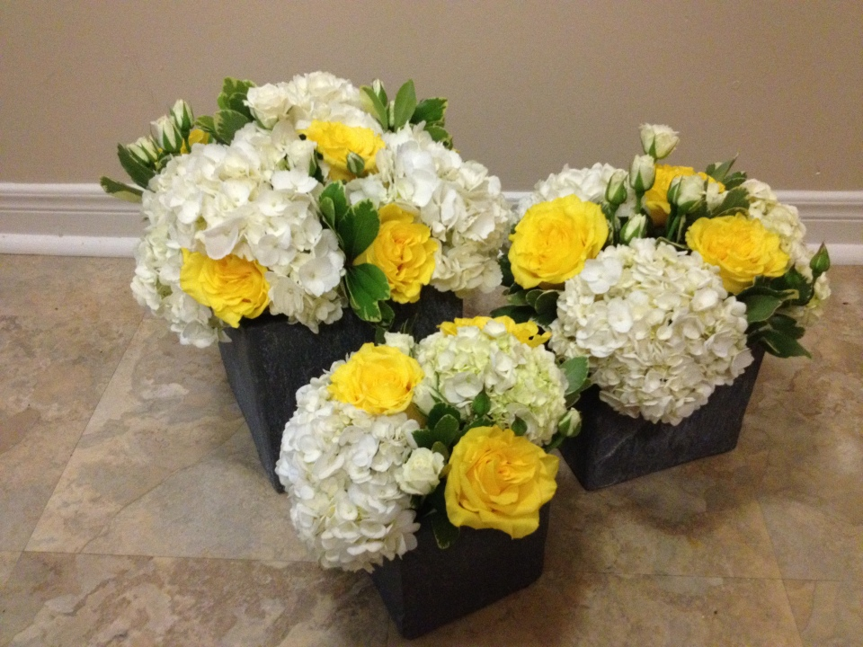 Centerpiece trios of hydrangea, roses and spray roses in stone containers