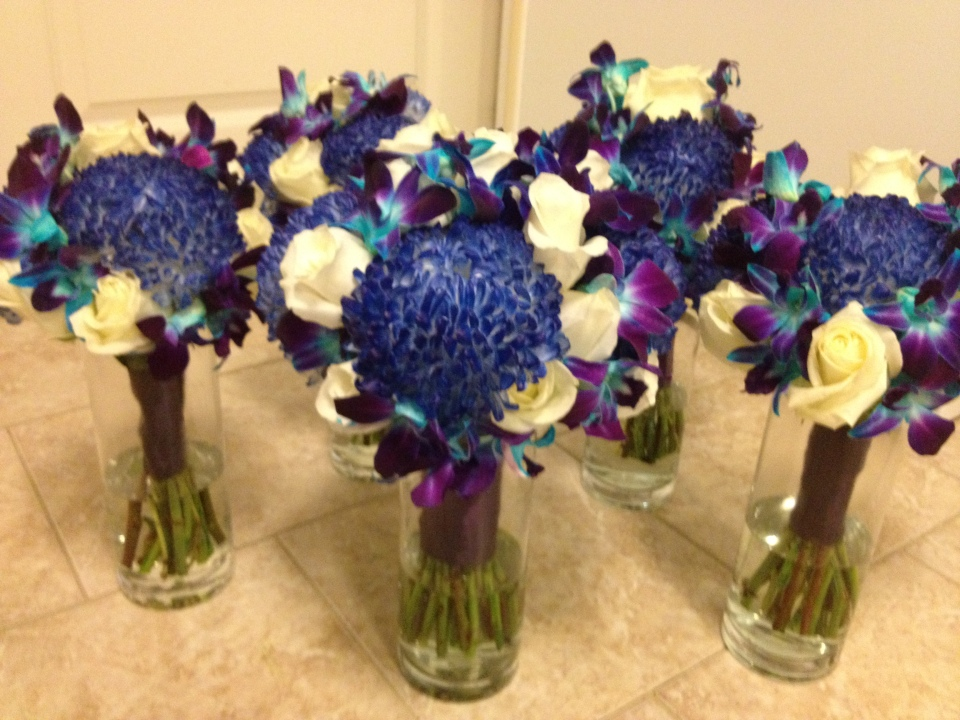 Bouquets of blue tinted mums, roses and dendrobium orchids.