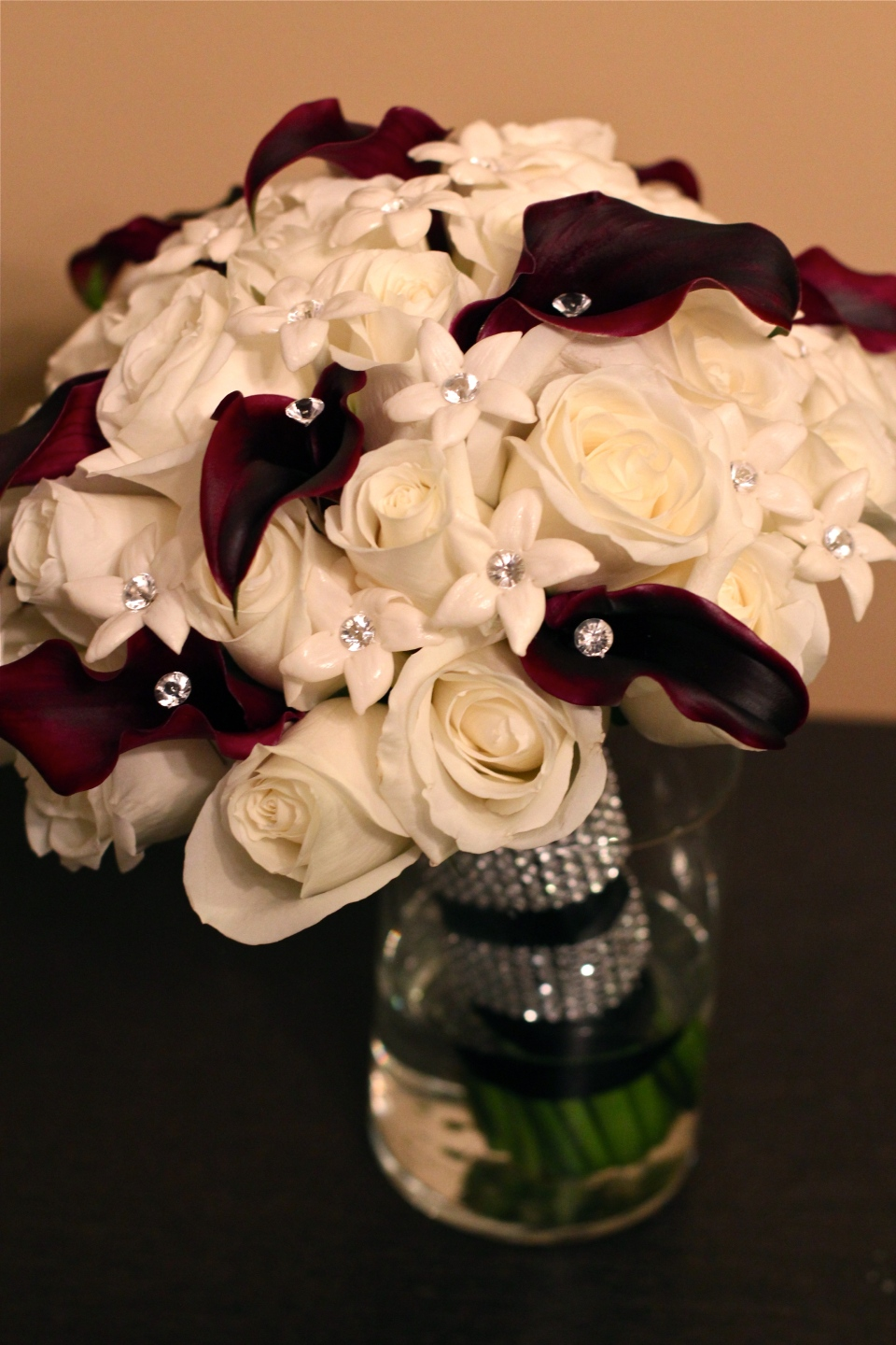 Bridal bouquet of white roses, stephanotis & black calla lilies.