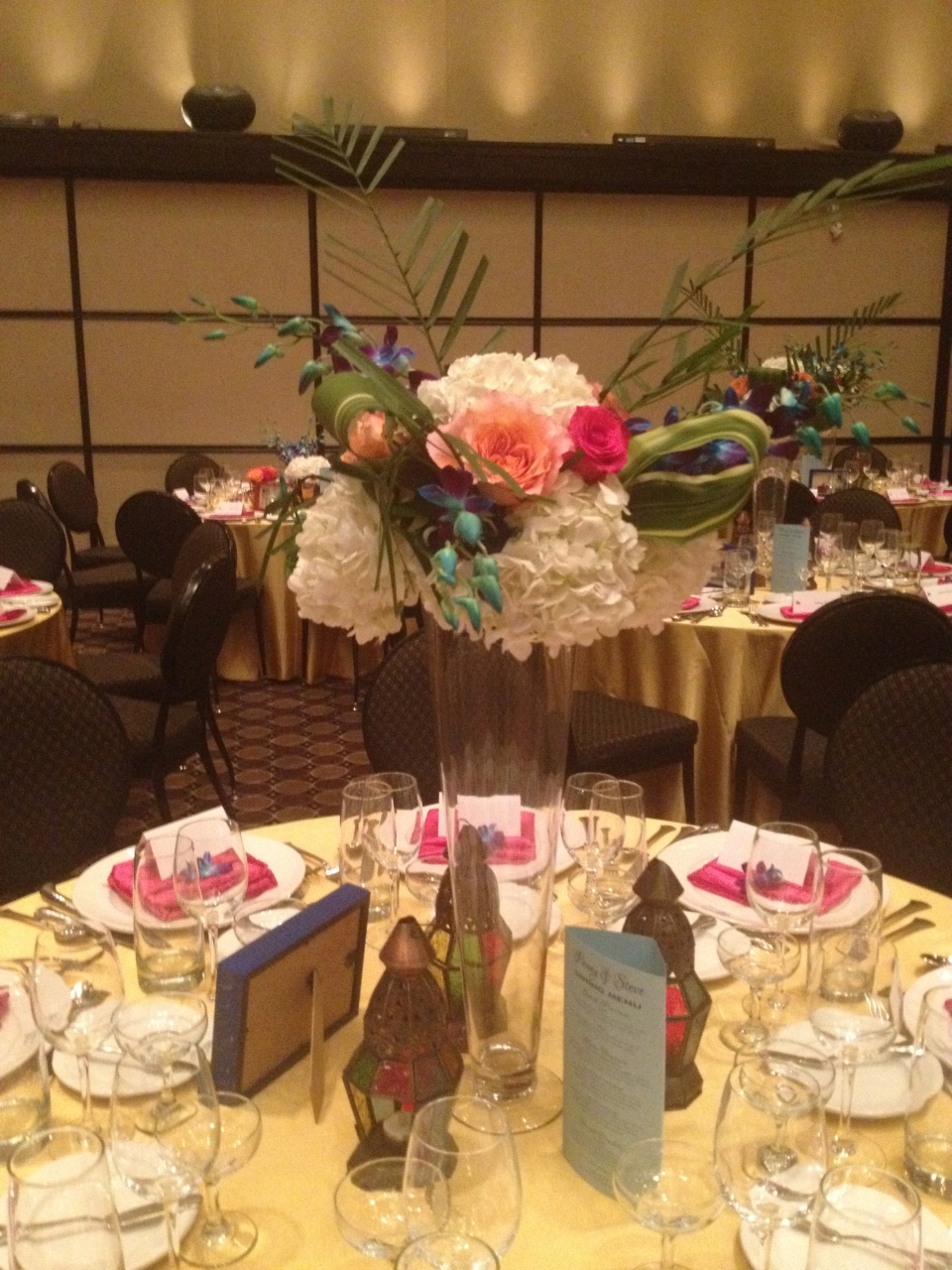 Tall centerpiece of hydrangea, roses, dendrobium orchids and palm fronds