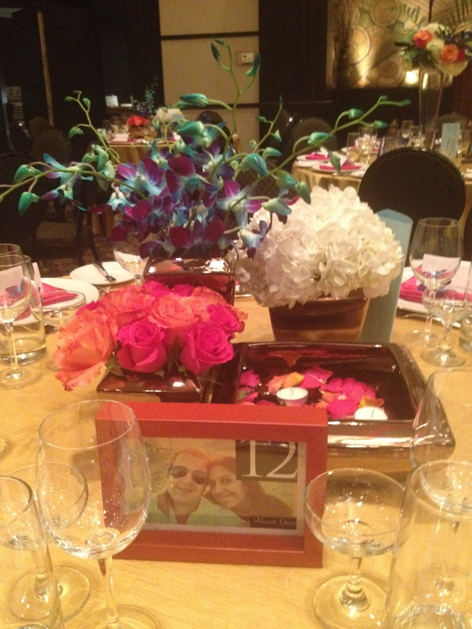 Cluster centerpiece of hydrangea, roses, dendrobium  orchids and floating candles